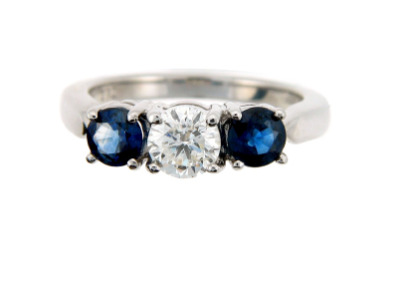Brilliant cut diamond engagement ring with sapphire side stones in white gold.