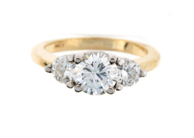 Brilliant cut diamond engagement ring with side stones in yellow gold.