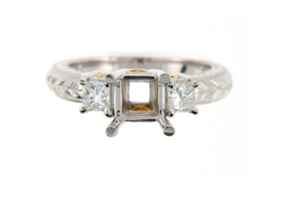 Hand engraved platinum engagement ring setting with princess cut side stones.