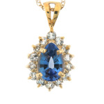 Pear cut sapphire and diamond pendant in yellow gold.